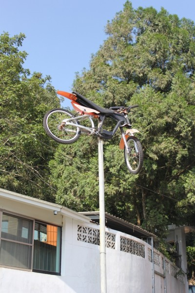 An orange dirt motor bike on a pole